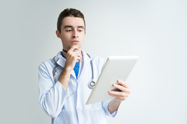 Pensive young male doctor using tablet computer Free Photo