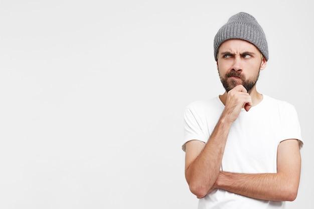 Задумчивый молодой человек в серой шляпе, поднял руку к лицу, касается его бороды, недовольно выглядит недоверчиво Бесплатные Фотографии