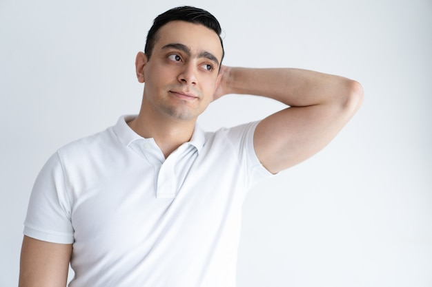 Pensive young man scratching back of head and looking away. handsome guy thinking. Free Photo