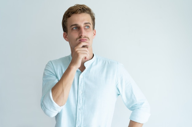 Pensive young man touching chin and looking away. handsome guy thinking. Free Photo