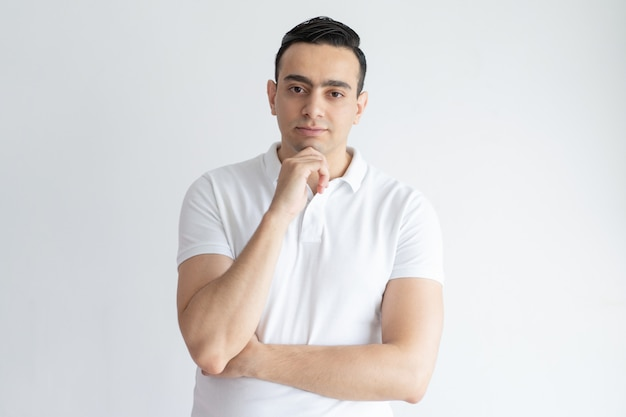 Pensive young man touching chin and looking at camera Free Photo