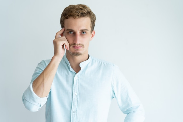 Pensive young man touching head with finger and looking at camera. Free Photo