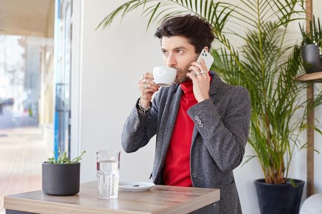 Pensieroso giovane uomo d'affari dai capelli scuri bere caffè e fare chiamate con il suo smartphone, guardando pensieroso avanti mentre posa su sfondo caffè Foto Gratuite