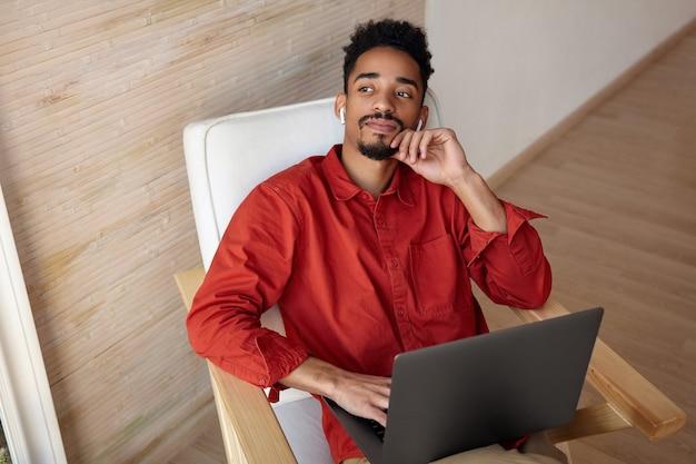 物思いにふける若い短い髪のブルネットの男は、顔に手を上げて、仕事で休憩しながらヘッドフォンで音楽を聴いています 無料写真