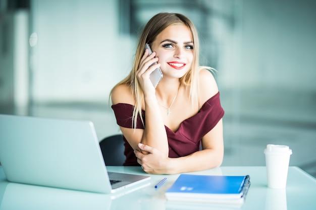 Задумчивая молодая женщина звонит оператору обновления программного обеспечения поддержки клиентов на портативном компьютере в офисе. серьезная женщина-фрилансер сосредоточилась на телефонном разговоре об онлайн-бизнесе Бесплатные Фотографии