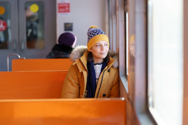 Pensive young woman traveling by local train in winter time, thinking, looking through the window. Premium Photo