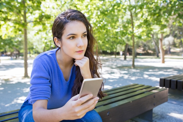 Pensive young woman using smartphone in park Free Photo