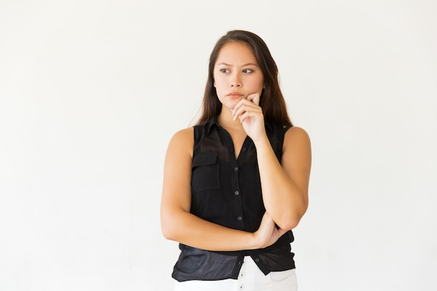 Pensive young woman with hand on chin Free Photo