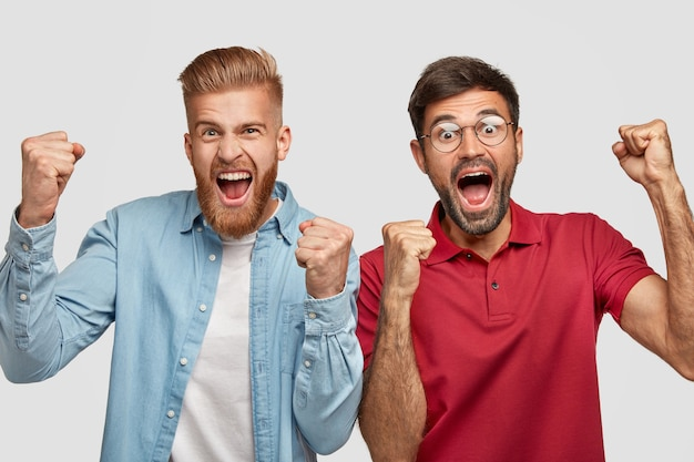 People, achievement and success concept. best male friends clench fists with happiness, being in high spirit, open mouthes widely, have overjoyed expressions, celebrate their winning, pose indoor Free Photo