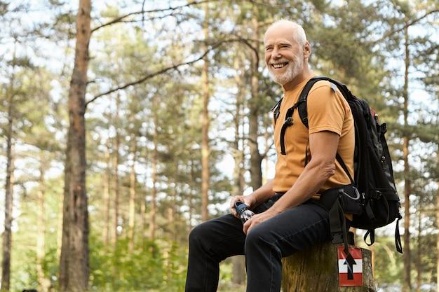 Люди, приключения, путешествия и концепция активного здорового образа жизни. веселый энергичный пожилой мужчина в походе с рюкзаком в лесу, отдыхая на пне, пьет воду с соснами в Бесплатные Фотографии