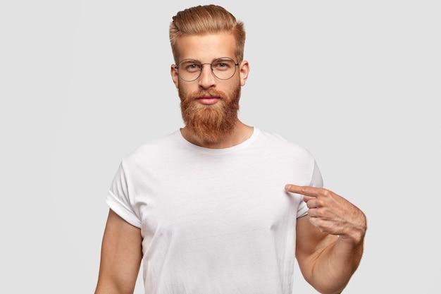 Concetto di persone, pubblicità e abbigliamento. hipster uomo serio con taglio di capelli alla moda e barba rossa, indica uno spazio vuoto della sua maglietta Foto Gratuite