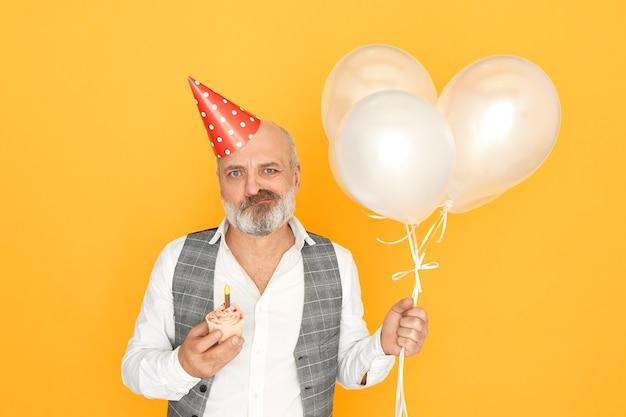 사람, 나이, 축하 및 휴가 개념. 심술 노인 사업가의 수평 샷 풍선, 원뿔 모자와 컵 케이크와 격리 된 포즈, 그의 은퇴를 축하, 불쾌한 표정을 갖는 무료 사진