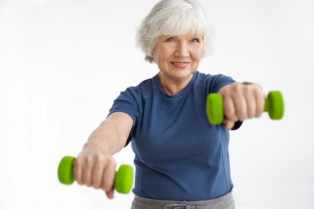 Concetto di persone, età, energia, forza e benessere. adorabile pensionato donna sorridente indossando t-shirt facendo esercizi fisici al mattino, utilizzando coppia di manubri verdi. messa a fuoco selettiva Foto Gratuite