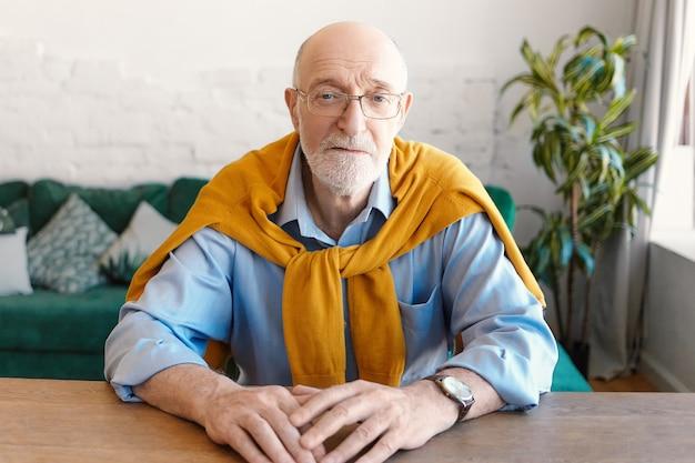 사람, 나이, 라이프 스타일 및 패션 개념. 직사각형 안경, 손목 시계, 파란색 셔츠와 노란색 스웨터를 입고 잘 생긴 형태가 이루어지지 않은 대머리 수석 남자가 나무 책상에 앉아 카메라를보고 무료 사진