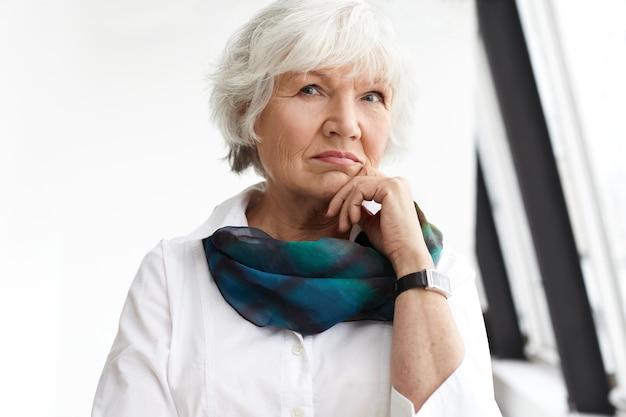 Люди, возраст, зрелость и концепция образа жизни. портрет стильной серьезной зрелой бизнес-леди с короткими белыми волосами, касающимися подбородка, задумчивой, думающей о бизнес-планах и идеях Бесплатные Фотографии