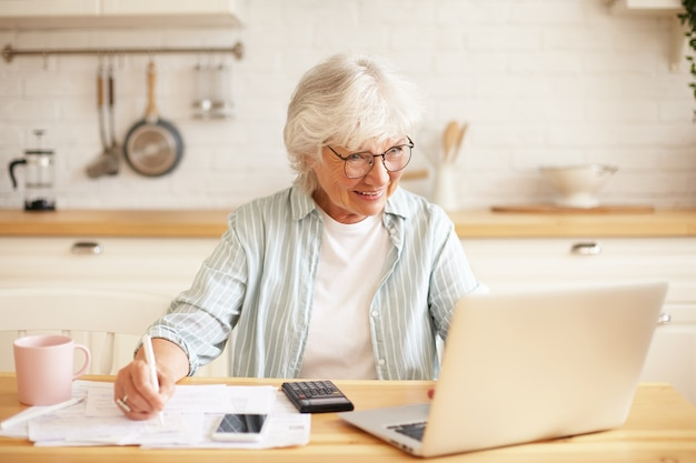 People, age, technology and occupation concept. indoor image of attractive smiling gray haired woman pensioner using laptop for remote work, sitting in kitchen with papers, earning money online Free Photo