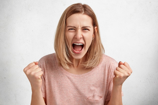 People and aggression concept. irritated young female model with bobbed hairdo, dressed in casual clothing, clenches fists in anger, has quarrel with husband Free Photo