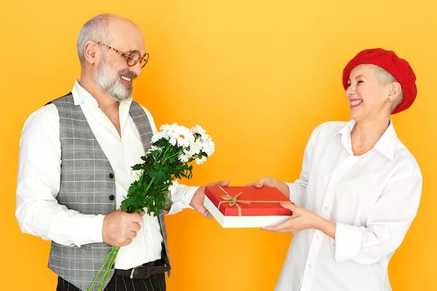 사람, 노화, 데이트 및 로맨스 개념. 필드 꽃의 무리와 초콜릿 상자를 들고 안경에 잘 생긴 우아한 수석 남자의 측면보기, 그의 매력적인 성숙한 여성 데이트 선물을주는 무료 사진