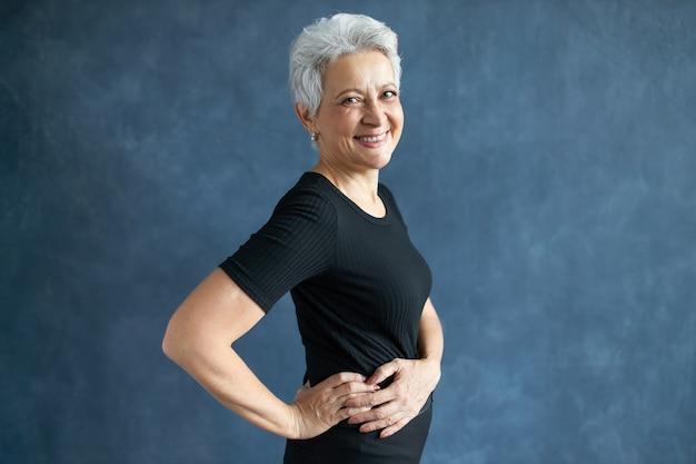 Люди, старение, зрелость и концепция образа жизни. студийное изображение веселой обрадованной зрелой женщины в черном облегающем топе, занимающейся физической активностью, позирует изолированно с руками на талии и смеется Бесплатные Фотографии