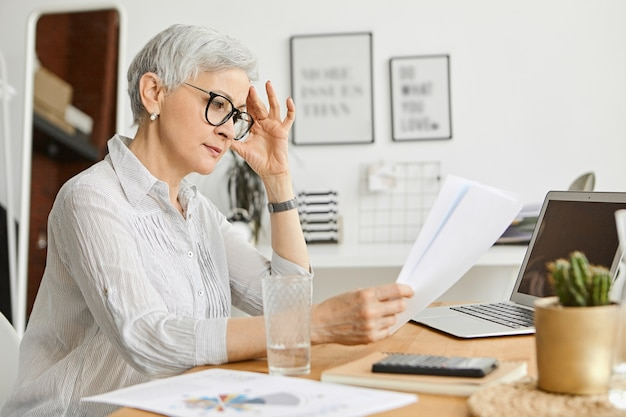 Люди, старение, технологии и концепция профессии. серьезная 50-летняя кавказская женщина в стильных очках и шелковой рубашке читает контракт, работая за столом, сидя перед открытым ноутбуком Бесплатные Фотографии