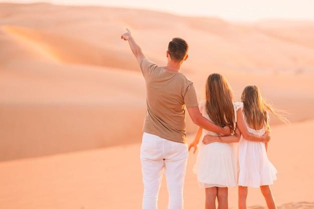 Люди среди дюн в пустыне в объединенных арабских эмиратах Premium Фотографии