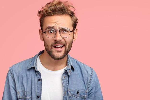 人と戸惑いのコンセプト。困惑した無精ひげを生やした白人男性が意外と眉を上げ、何かに感動し、白いtシャツとデニムシャツを着て、ピンクの壁にポーズをとる 無料写真