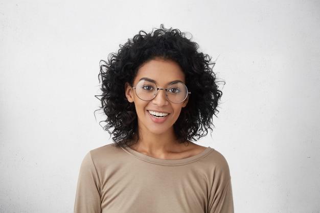 Люди и образ жизни. эмоции и чувства. симпатичная позитивная темнокожая студентка в повседневной одежде и стильных круглых очках счастливо улыбается, радуясь первому дню в университете Бесплатные Фотографии
