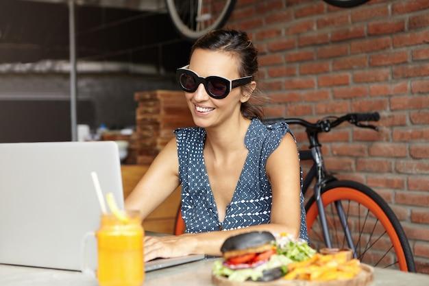 Люди и современные технологии. красивая женщина в модных солнцезащитных очках, наслаждаясь бесплатным wi-fi, сидя перед открытым ноутбуком с едой на столе. женский фрилансер с помощью портативного компьютера для удаленной работы Бесплатные Фотографии
