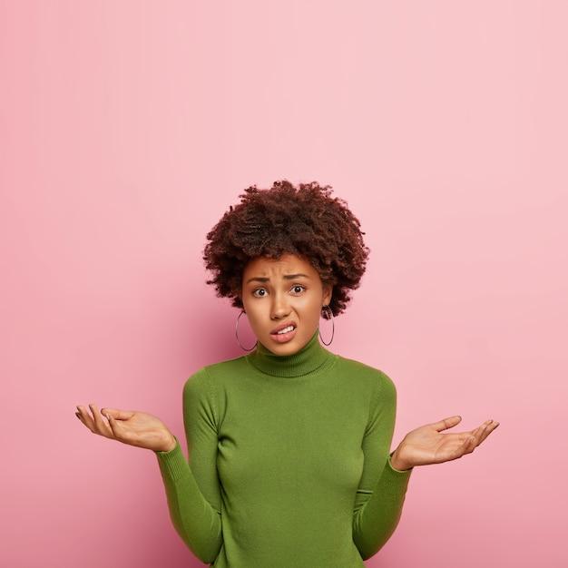 人と不確実性の概念。不機嫌な躊躇している女性モデルは、疑いを持って手のひらを広げ、紛らわしく見え、緑のセーターを着て、ピンクの壁にポーズをとり、スペースを上向きにコピーします 無料写真