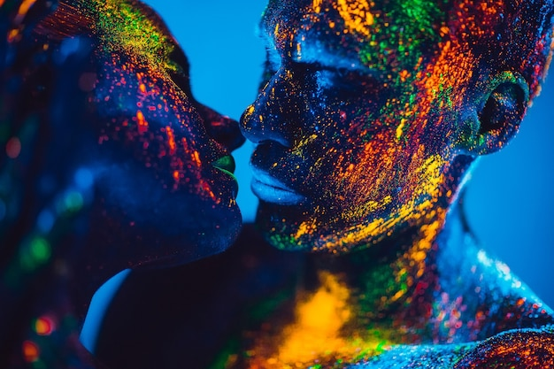 People are colored fluorescent powder. a pair of lovers dancing at a disco. Premium Photo