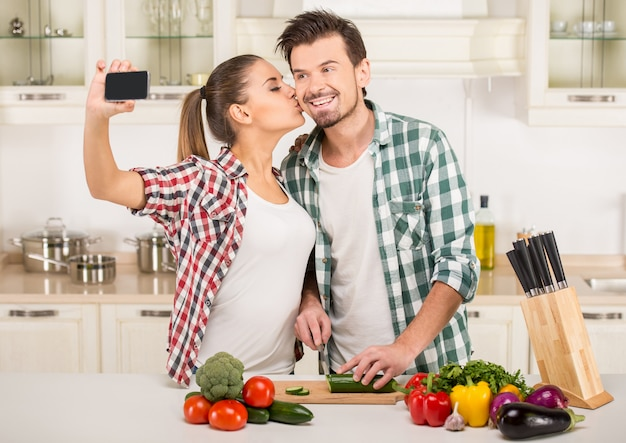 People are cooking, kissing and taking a photo. Premium Photo