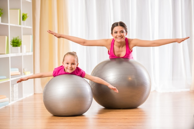 People are doing physical exercises on fitness ball at home. Premium Photo