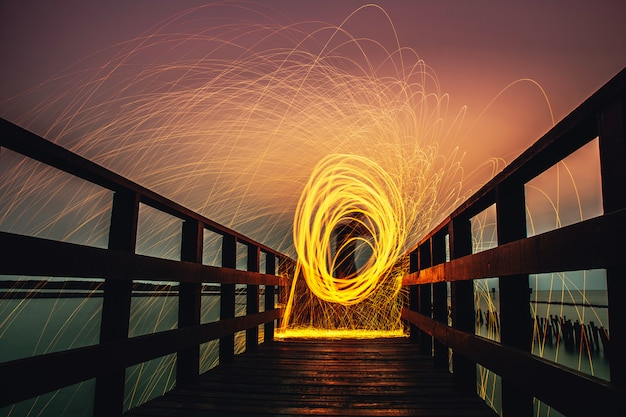 People are holding fireworks and spin on long bridge view at sea landscapes Premium Photo