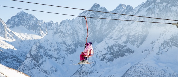 People are lifting on open lift high up in caucasus mountains Premium Photo