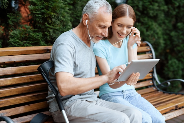 People are sitting on a bench in the park with tablet Premium Photo