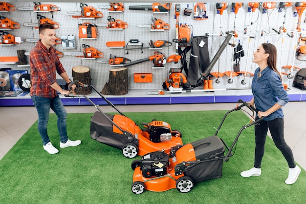 People are testing the lawn mower in the store. Premium Photo