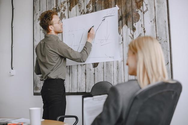 人々はプロジェクトに取り組んでいます。テーブルに座っているスーツを着た男性と女性。ビジネスマンは、スタンドにグラフを描きます。 無料写真