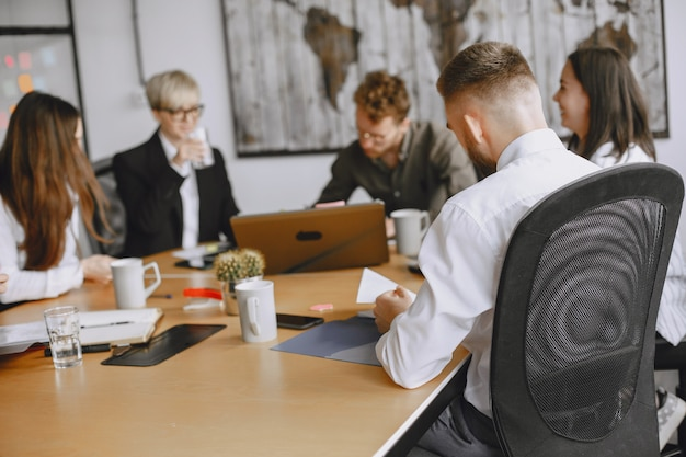 人々はプロジェクトに取り組んでいます。テーブルに座っているスーツを着た男性と女性。ビジネスマンはラップトップを使用します。 無料写真
