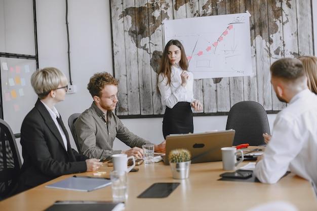 人々はプロジェクトに取り組んでいます。テーブルに座っているスーツを着た男性と女性。女性はスタンドにグラフを描きます。 無料写真