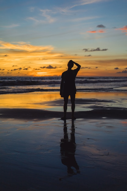 People on the beach at sunset. the girl is jumping against ...