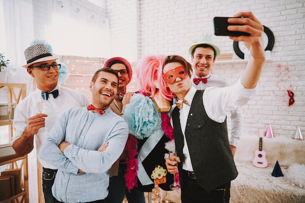 People in bow ties taking selfie on phone at party. Premium Photo