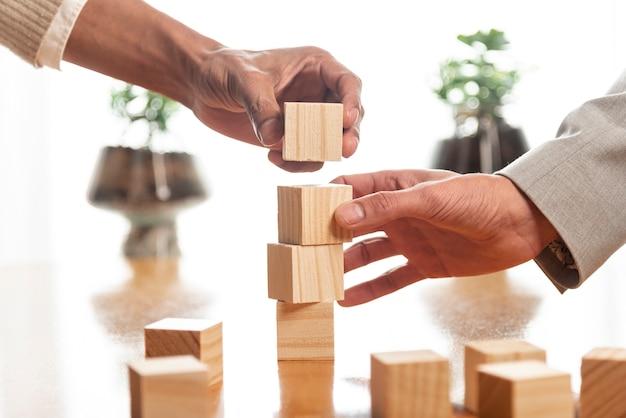 Люди строят груды деревянных кубиков Premium Фотографии
