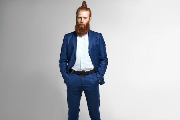사람, 비즈니스, 직업, 스타일, 패션 및 남성복 개념. 우아한 파란색 양복과 머리 롤빵을 입고 좋은 찾고 젊은 백인 수염 난 남성 회사원, 주머니에 손을 스튜디오에서 포즈 무료 사진