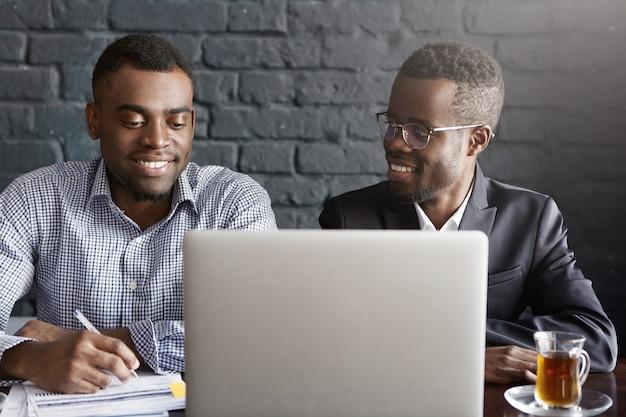 人、ビジネス、チームワーク、協力の概念。現代のオフィスで一般的なラップトップコンピューターの一般的なプレゼンテーションに一緒に取り組んでいるフォーマルな服装の2人のアフリカ系アメリカ人企業の労働者 無料写真