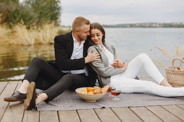 Persone in riva al fiume. delizioso picnic estivo sano sull'erba. frutta su un blancet. Foto Gratuite