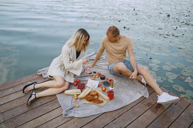 Люди у реки. вкусный здоровый летний пикник на траве. фрукты на бланшете. Бесплатные Фотографии
