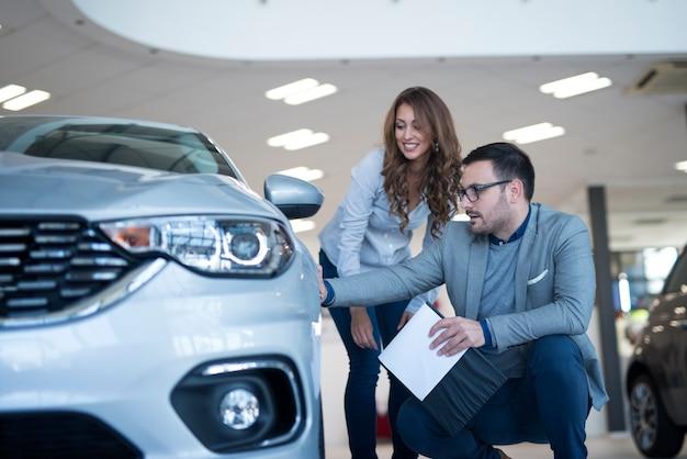Persone nello showroom di concessionaria auto discutendo di nuovo veicolo Foto Gratuite