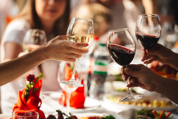People celebrate and raise glasses of wine for toast Premium Photo