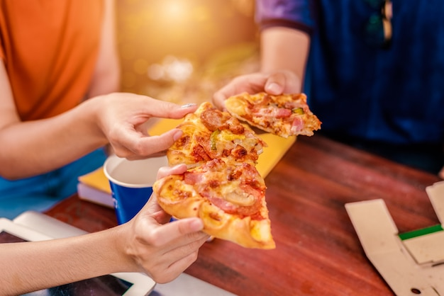 People celebrating with pizza in hand. food and friendship concept. lifestyles theme Premium Photo