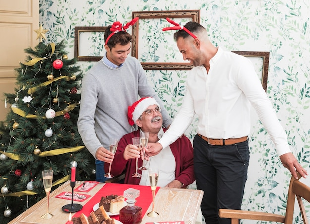People clanging glasses of champagne near festive table Free Photo